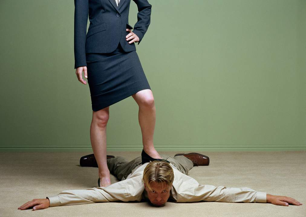 Woman standing with one foot on man spreadeagled on floor